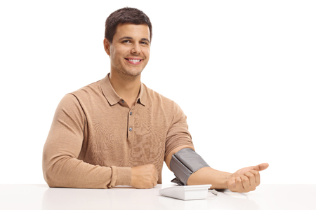 Young guy seated at a table measuring his blood pressure isolated on white background