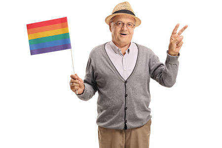 Mature man holding a rainbow flag and making a peace gesture isolated on white background