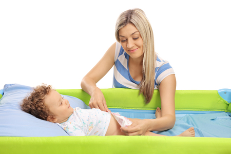 Young mother changing a diaper on her baby son isolated on white background Stock Photo
