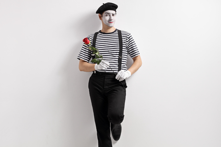 Mime with a rose flower leaning against a wall