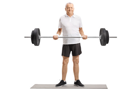 Full length portrait of a senior standing on an exercise mat and lifting a barbell isolated on white background