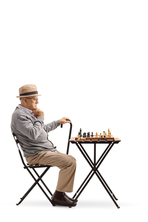 Pensive mature man looking at a chessboard isolated on white background
