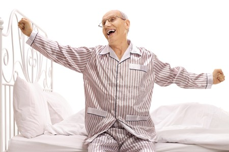 Elderly man in pajamas sitting on a bed stretching himself isolated on white background