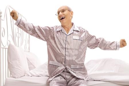 Oudere man in pyjama zittend op een bed uitrekken zich geïsoleerd op een witte achtergrond