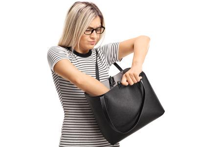 mujer joven enojado que mira en su bolso aislado en el fondo blanco