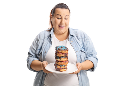 Oveweight female looking at a pile of doughnuts on a plate isolated on white background