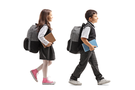 Schoolgirl and schoolboy with backpacks walking  isolated on white background Stock Photo