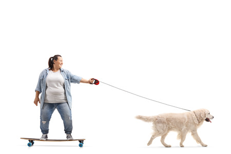 Full length profile shot of a young woman on a longboard walking a dog isolated on white background 免版税图像