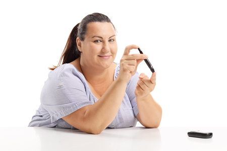 Overweight woman measuring her blood sugar level with a glucometer isolated on white background