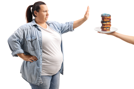 Overweight woman refusing to eat donuts isolated on white background Stock Photo