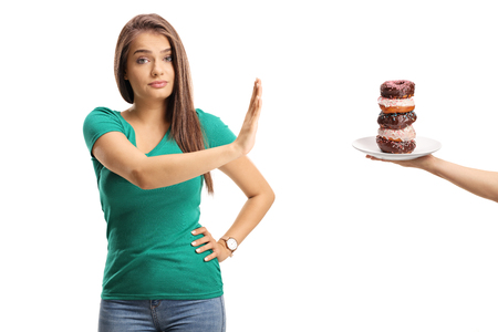 Young woman refusing a plate of donuts isolated on white background