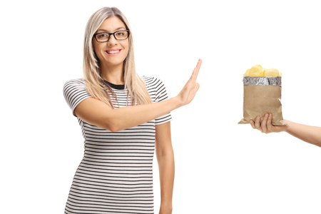 Young woman refusing a bag of potato chips isolated on white background