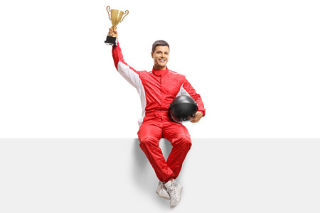 Winner racer in a suit holding a gold trophy cup and sitting on a panel isolated on white background