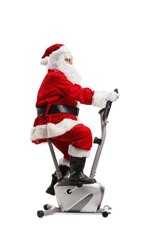 Santa Claus riding a stationary bicycle isolated on white background