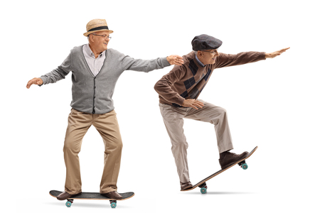 Full length profile shot of two elderly men skateboarding isolated on white background