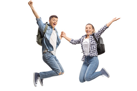 Happy male and female students jumping isolated on white background