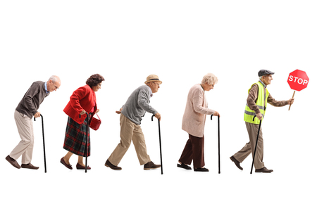Full length shot of senior people walking in a line behind an elderly man with a safety vest and stop sign isolated on white background Foto de archivo