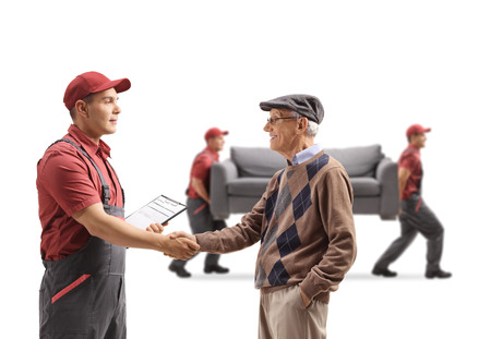 Senior man shaking hands with a mover, movers carrying a couch in the back isolated on white background