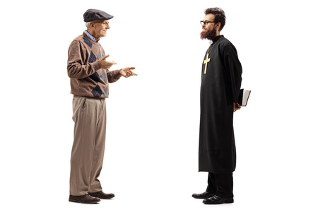 Full length shot of an elderly man talking to a priest isolated on white background Stock Photo