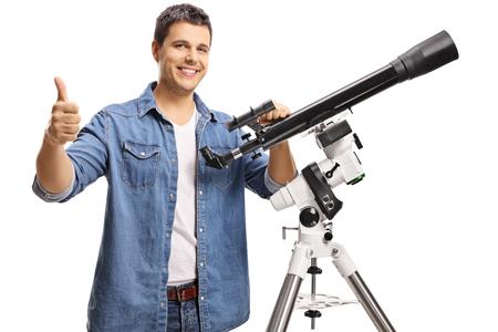 Joven sonriente con un telescopio mostrando los pulgares para arriba aislado sobre fondo blanco. Foto de archivo