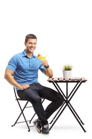 Young man sitting at a table and holding a cocktail isolated on white background
