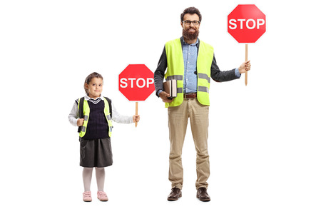 Full length portrait of a schoolgirl and a teacher with safety vests and stop signs isolated on white background
