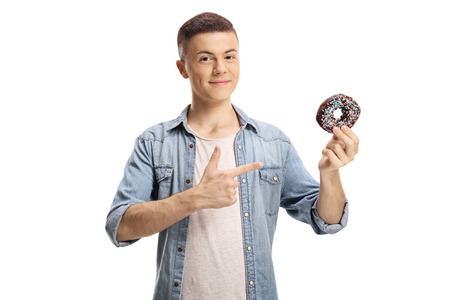 Young man holding a chocolate donut and pointing isolated on white background