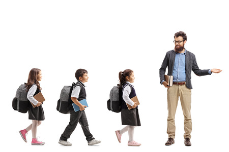 Full length profile shot of schoolchildren walking in a line and a teacher gesturing welcome with his hand