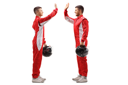 Full length profile shot of two racers high-fiving each other