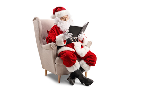 Santa Claus sitting in an armchair and reading a book Foto de archivo