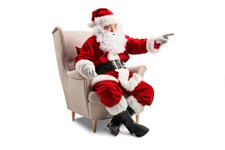 Santa Claus sentado en un sillón y apuntando