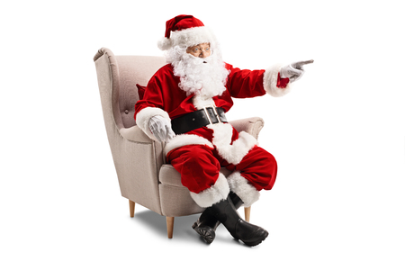 Santa Claus sitting in an armchair and pointing Stockfoto