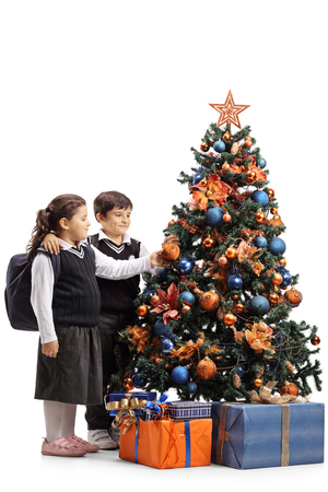 Full length shot of a schoolgirl and schoolboy decorating a Christmas tree isolated on white
