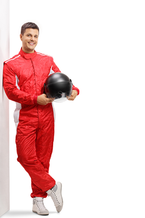 Full length portrait of a racer holding a helmet and leaning against a wall Stockfoto