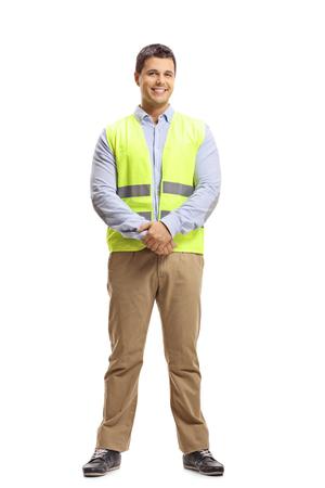 Retrato de cuerpo entero de un hombre joven con un chaleco de seguridad mirando a la cámara y sonriendo
