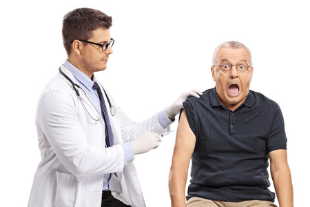 Young doctor giving a shot to a terrified mature man