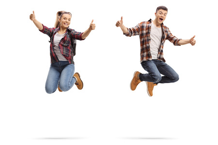 Teen boy and girl jumping and showing thumbs up