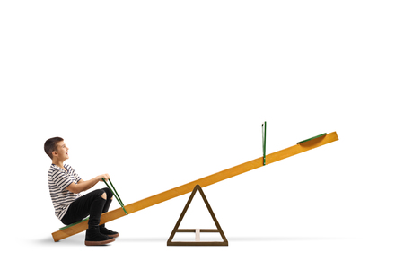 Full length shot of a smiling boy sitting alone on a seesaw isolated on white
