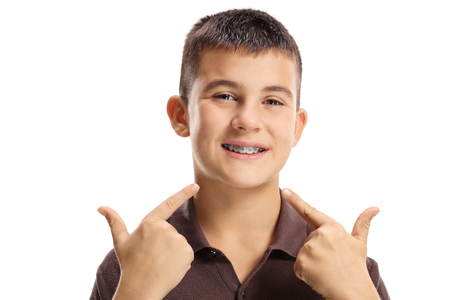 Boy with dental braces pointing on the mouth with both fingers isolated on white