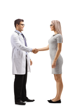 Full length profile shot of a woman shaking hands with a doctor isolated on white