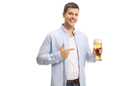 Handsome young man holding a pint of beer and pointing at it isolated on white