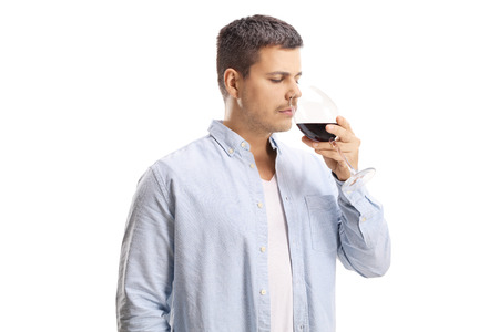 Young man smelling a glass of wine isolated on white