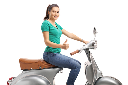 Young female sitting on a vintage scooter and showing thumbs up isolated on white
