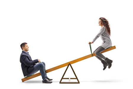 Young man and woman playing on a seesaw isolated on white Standard-Bild
