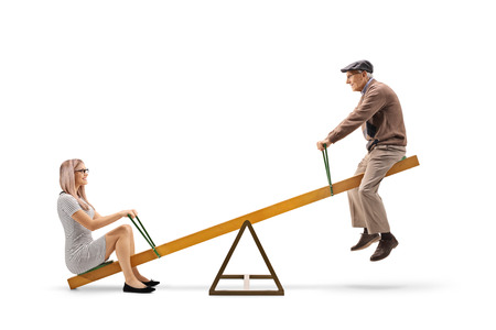Young woman and a senior man playing on a seesaw isolated on white