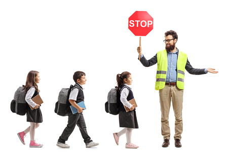 Full length shot of schoolchildren walking in a line and a teacher with a safety vest