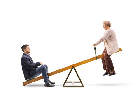 Young guy and an elderly woman on a seesaw isolated on white 版權商用圖片
