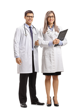 Full length portrait of a male and female doctor smiling at the camera isolated on white 版權商用圖片