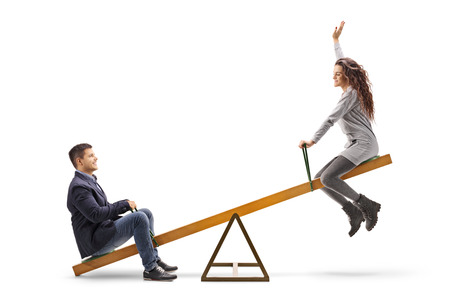 Young couple on a seesaw isolated on white