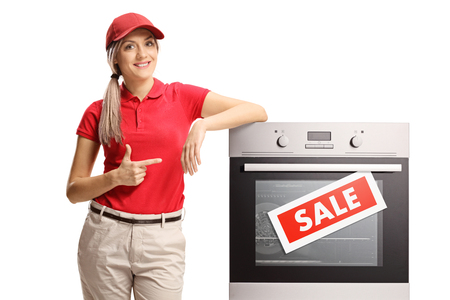 Young saleswoman pointing to an electrical oven on sale isolated on white Stockfoto